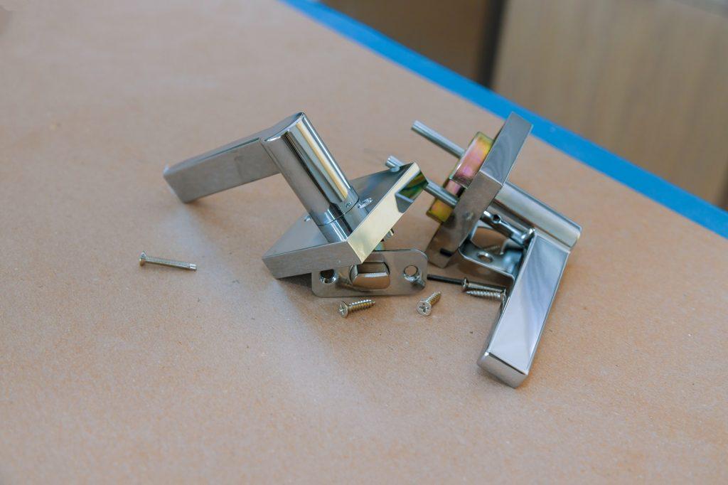 Assembling a new doorknob the closeup of worker hands installing new door locker